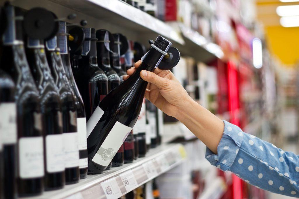 A woman chooses a bottle of wine on a supermarket shelf