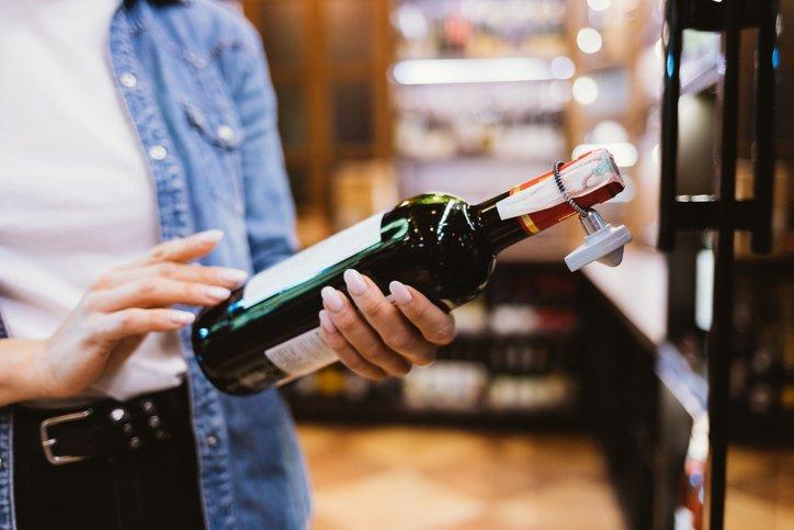 Woman reads a wine bottle label in a supermarket