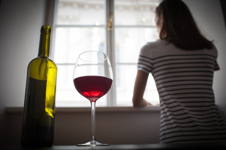 Woman looks out of window with a glass of wine next to her