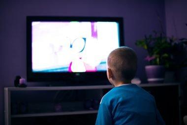 Boy watching television in dark living room